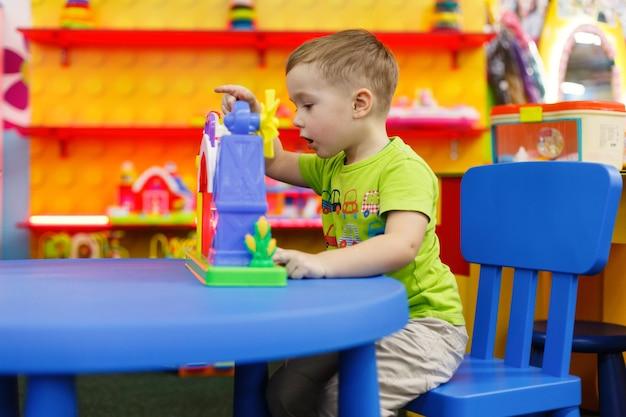 Szczęśliwe dziecko z ciekawą zabawką w przedszkolu i przedszkolu chłopiec bawi się kolorową zabawką