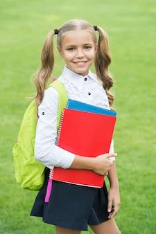 Szczęśliwe dziecko z długimi włosami ogony w mundurek szkolny trzymać książki do nauki na zewnątrz, wiedza.