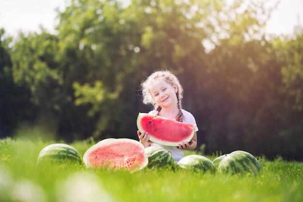 Szczęśliwe dziecko z dużym czerwonym kawałkiem arbuza siedzi na zielonej trawie w parku latem. koncepcja zdrowego odżywiania.