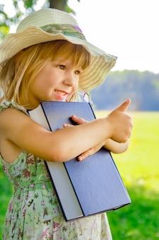Szczęśliwe dziecko z książką o naturze biblii w parku