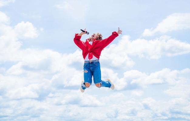 Szczęśliwe dziecko z mikrofonem. koncepcja karaoke. śpiewać piosenki. koncepcja życia i ludzi. spraw, aby twój głos był głośniejszy. teen dziewczyna śpiewa piosenkę z mikrofonem. mieć imprezę. skakać tak wysoko.