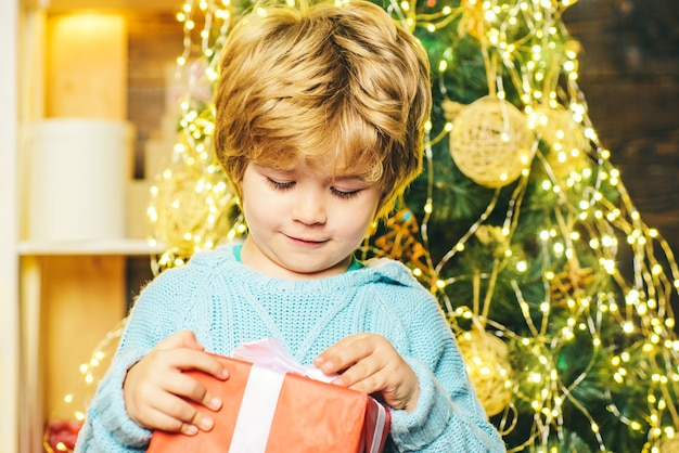 Szczęśliwe dziecko z prezentem na boże narodzenie. portret dziecka santa z prezentem patrząc na kamery. kid zabawy