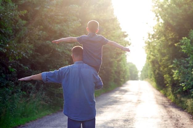 Szczęśliwe dziecko z rodzicem na ramionach idzie wzdłuż drogi w tle parku park