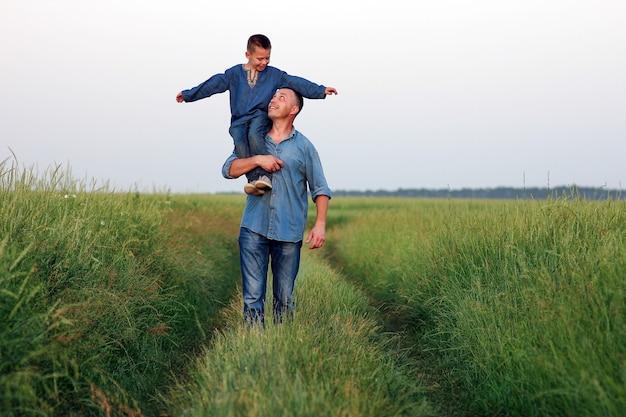 Szczęśliwe dziecko z rodzicem na ramionach idzie wzdłuż drogi w tle parku