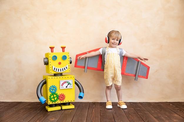 Szczęśliwe dziecko z tekturowymi skrzydłami