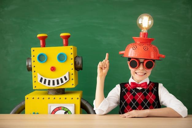 Szczęśliwe dziecko z zabawkowym robotem w szkole