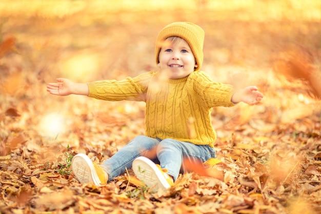 Szczęśliwe dziecko zabawy na świeżym powietrzu w jesiennym parku