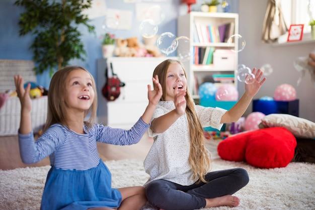 Szczęśliwe dziewczyny bawiące się bąbelkami