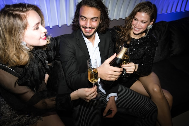 Szczęśliwe dziewczyny i młody elegancki mężczyzna siedzi na kanapie w klubie nocnym i opiekania szampanem na imprezie