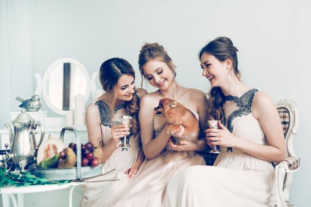 Szczęśliwe dziewczyny i panna młoda siedzi w buduarze. święta i imprezy
