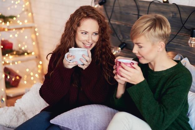 Szczęśliwe dziewczyny piją herbatę w łóżku