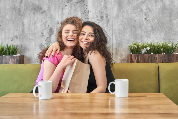Szczęśliwe dziewczyny przytulanie, trzymając papierową torbę obecny w kawiarni.