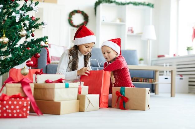 Szczęśliwe dziewczyny rozpakowują prezenty świąteczne