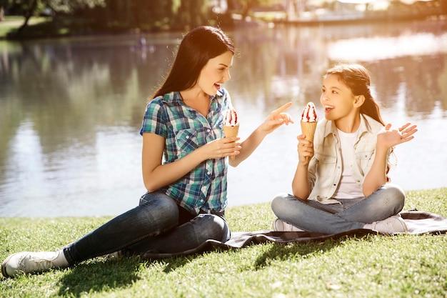 Szczęśliwe dziewczyny siedzą razem na trawie. młoda kobieta sięga do lodów jej córki ręką i uśmiecha się. ona też ma lody. dziewczyny patrzą na mamę i uśmiechają się.
