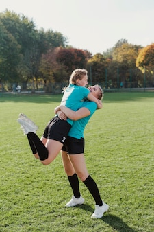 Szczęśliwe dziewczyny sportowe, obejmując się nawzajem