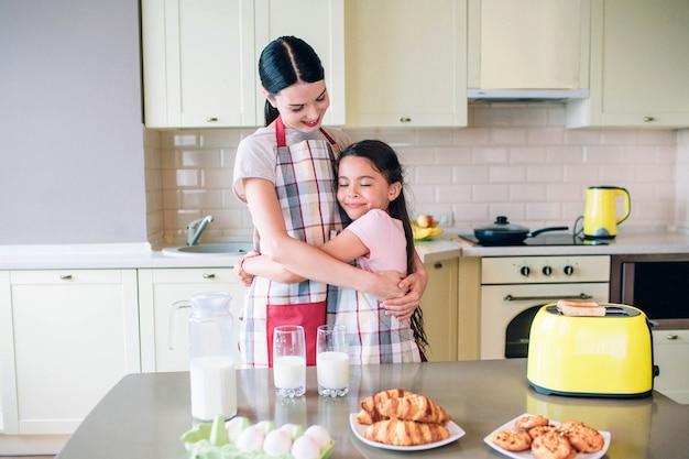 Szczęśliwe dziewczyny stoją razem w kuchni i uśmiechają się. przytulają się. mama patrzy na córkę. na stole jest smaczne jedzenie.