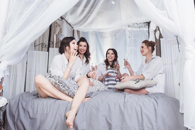 Szczęśliwe dziewczyny w białych koszulach męskich, które świętują wieczór panieński