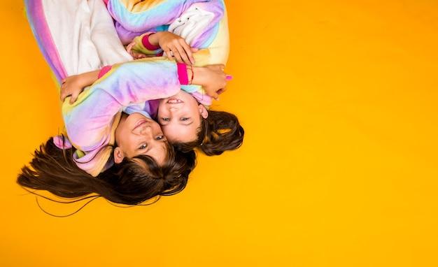 Szczęśliwe dziewczyny w pluszowych kombinezonach leżą na żółtym tle z miejscem na tekst