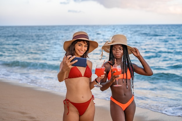 Szczęśliwe dziewczyny z koktajlami robiące selfie w pobliżu morza