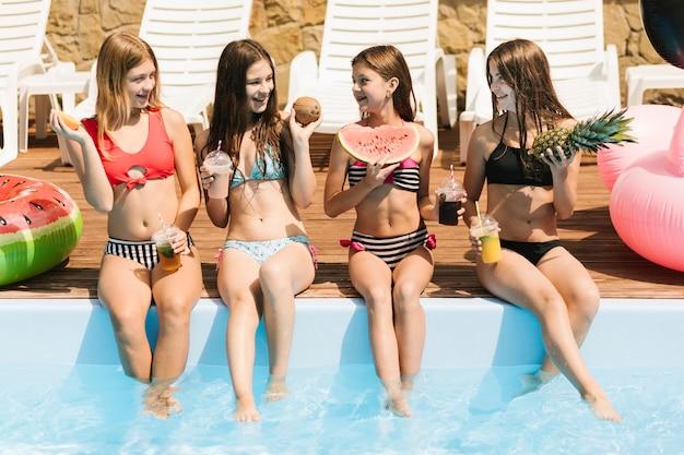 Szczęśliwe dziewczyny z owocami przy pływackim basenem