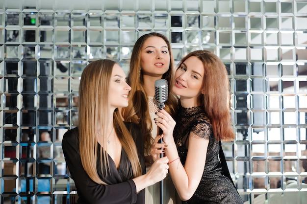 Szczęśliwe dziewczyny zabawy śpiewają na imprezie