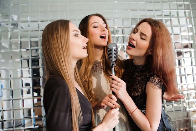 Szczęśliwe dziewczyny zabawy śpiewają na imprezie.