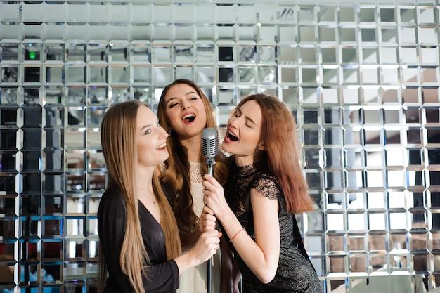Szczęśliwe dziewczyny zabawy śpiewając na imprezie