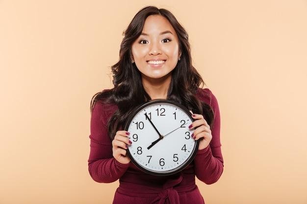 Szczęśliwe emocje azjatykciej kobiety z kędzierzawym długie włosy mienie zegarem pokazuje prawie 8 czekania na coś przyjemnego nad brzoskwini tłem