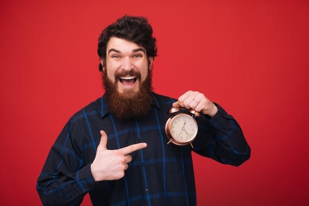 Szczęśliwe godziny. umiejętności zarządzania czasem. mężczyzna brodaty dojrzały faceta chwyta zegar odizolowywający nad czerwieni ścianą