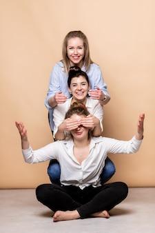 Szczęśliwe i otyłe wielokulturowe kobiety w stanikach na beżowym tle. różnorodne piękno. trzy wieloetniczne panie owinięte w ręczniki pozują uśmiechając się do kamery na beżowym tle. ujęcie studyjne