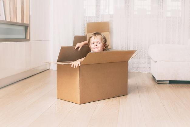 Szczęśliwe i piękne dziecko uśmiecha się w domu w salonie siedząc w kartonowym pudełku