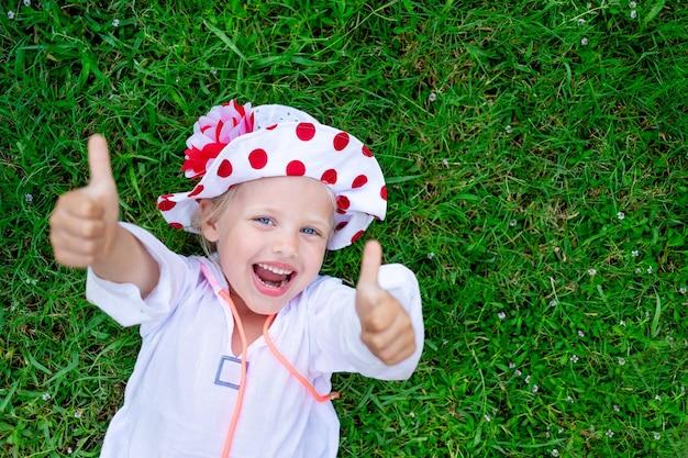 Szczęśliwe i radosne dziecko dziewczynka leży na zielonej trawie trawnika i w kapeluszu panama w lecie i pokazuje klasę i uśmiecha się