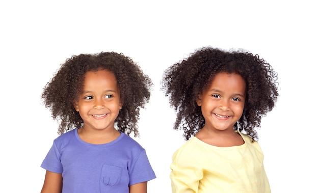 Szczęśliwe identyczne siostry na białym tle