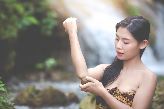 Szczęśliwe kąpiące się kobiety przy naturalnym siklawą