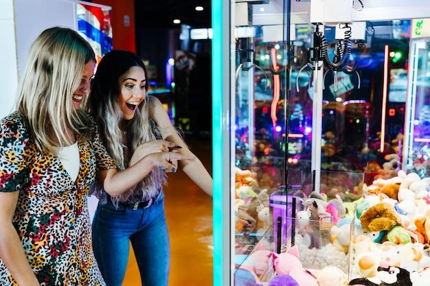 Szczęśliwe kobiety bawić się arkadową maszynę