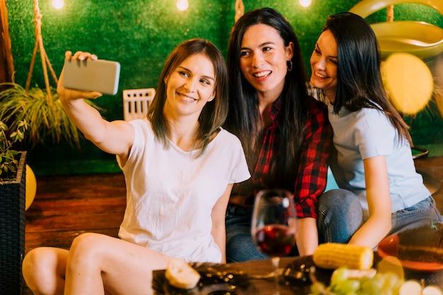 Szczęśliwe kobiety bierze selfie przy przyjęciem