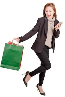 Szczęśliwe kobiety dziury torba i smartphone na zakupy