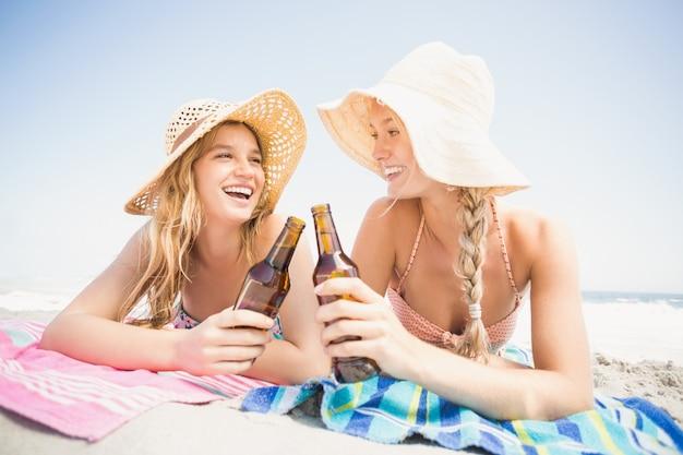 Szczęśliwe kobiety kłama na plaży z piwną butelką