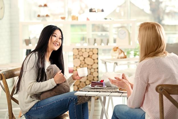 Szczęśliwe kobiety odpoczywające w kociej kawiarni