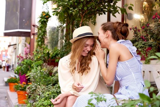 Szczęśliwe kobiety opowiada i śmia się w parku z zielonym tłem