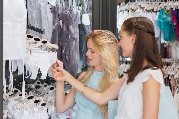 Szczęśliwe kobiety patrzeje bieliznę w zakupy centrum handlowym