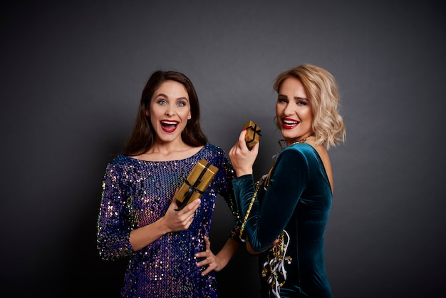 Szczęśliwe kobiety posiadające złote prezenty na czarno