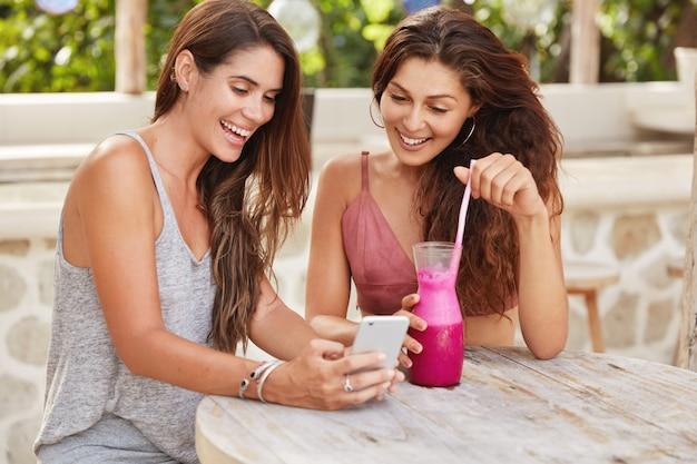 Szczęśliwe kobiety prowadzą zabawne rozmowy online na smartfonie, cieszą się wolnym czasem w kawiarni przy świeżym letnim drinku