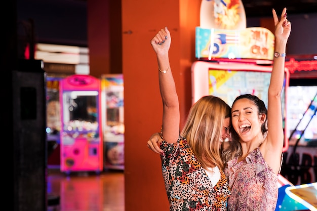 Szczęśliwe kobiety przy arkadą rozrywki
