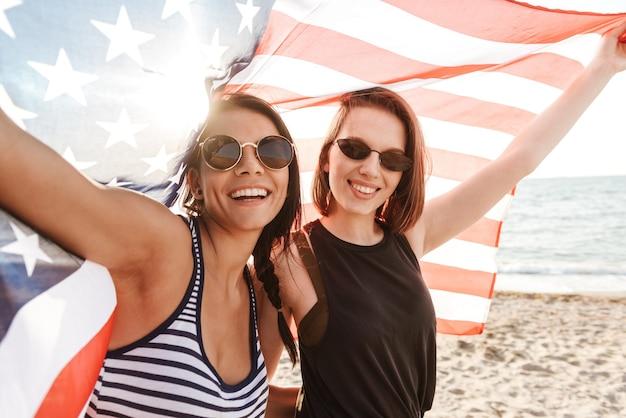 Szczęśliwe kobiety przyjaciele na zewnątrz na plaży trzymając flagę usa zabawy