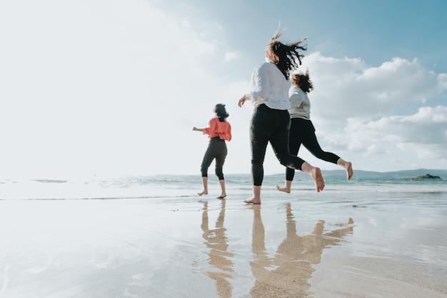 Szczęśliwe kobiety przyjaciół biegnie na plaży w jasny dzień, przyjaciele szczęśliwi relaksują się, bawiąc się na plaży w pobliżu morza, gdy zachód słońca wieczorem.