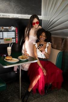 Szczęśliwe kobiety siedzą przy stole pełny strzał