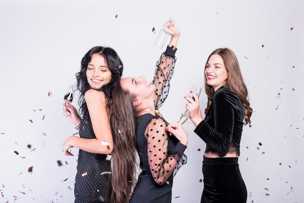 Szczęśliwe kobiety tanczy z szkłami szampan
