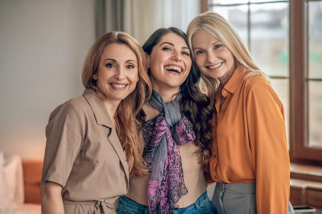 Szczęśliwe kobiety. trzy kobiety w eleganckich strojach uśmiechnięte i wyglądające na szczęśliwe