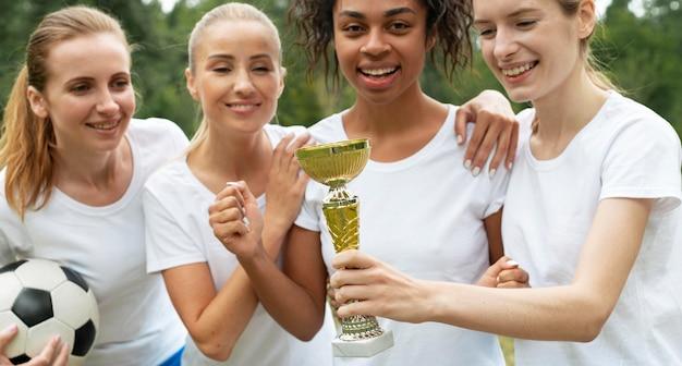 Szczęśliwe kobiety trzymające puchar zwycięzców